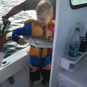 Young boy holding caught fish